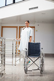 Smiling patient standing next to a wheelchair