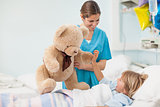 Nurse showing a teddy bear to a child