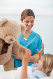 Smiling nurse showing a teddy bear to a child