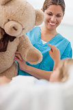 Happy nurse holding a teddy bear
