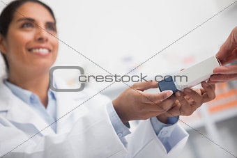 Close up of a smiling pharmacist giving a box to someone
