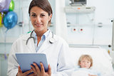 Doctor holding a tablet computer next to a child