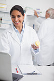 Female pharmacist holding a drug box while smiling