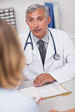 Doctor sitting at his desk looking at a patient
