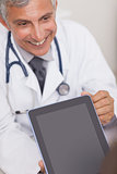 Doctor holding a tablet computer while smiling