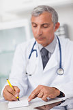Doctor writing on a notepad at his desk