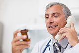 Doctor looking at a drug bottle while calling
