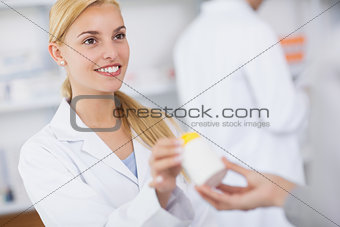 Blonde pharmacist giving a drug box