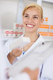 Blonde pharmacist holding a drug box while smiling