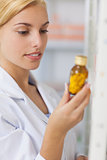 Blonde pharmacist looking at a drug bottle