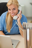 Blonde nurse calling while looking at camera