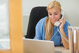 Blonde nurse calling next to a laptop