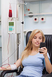 Female blood donor looking at her mobile phone