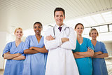 Smiling doctor and nurses with arms crossed