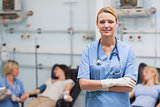 Nurse standing with arms crossed next to patients