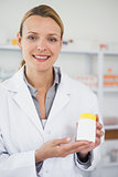 Smiling pharmacist presenting a drug box