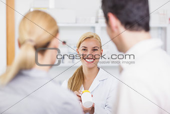 Blonde pharmacist holding a drug box