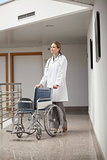 Serious doctor pushing a wheelchair in the corridor