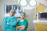 Serious surgeon and a nurse looking at camera