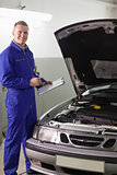 Smiling mechanic holding a clipboard and a pen