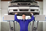 Smiling mechanic touching the below of a car