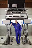 Smiling mechanic standing below a car