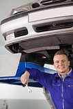 Smiling mechanic holding a spanner below a car