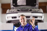 Smiling mechanic doing a gesture with his fingers