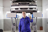 Smiling mechanic standing with thumb up