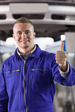 Mechanic standing with thumb up next to a car