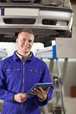 Smiling mechanic holding a tablet computer