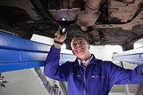 Smiling mechanic illuminating a car with a flashlight