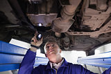 Concentrated mechanic illuminating a car with a flashlight