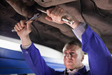 Concentrated mechanic repairing a car while using tools