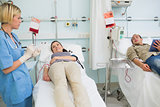 Two transfused patients looking at a nurse