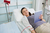 Smiling transfused holding a tablet computer