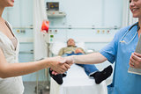 Nurse shaking hand of a patient