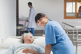 Smiling nurse leaning on the bed of a patient