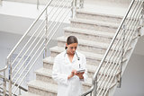Doctor using a tablet computer on stairs