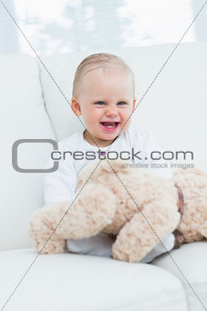 Baby smiling with teddy bear on his knees