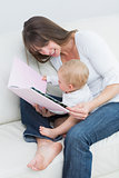 Baby holding a book with a mother