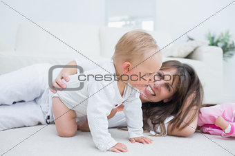 Baby on all fours next to his mother