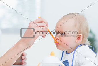 Baby with a plastic spoon on his mouth
