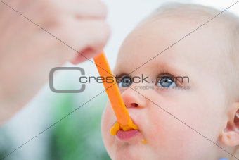 Baby looking at his mother while eating