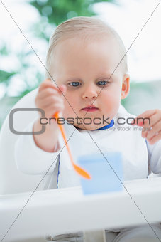 Baby looking at a plastic spoon while holding it