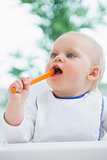 Baby holding a plastic spoon while putting it in his mouth