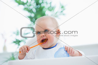 Baby holding a spoon while putting it in his mouth