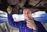 Smiling man repairing a car with his thumb up