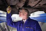Man looking at the below of a car while repairing