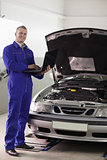 Mechanic standing while holding a computer